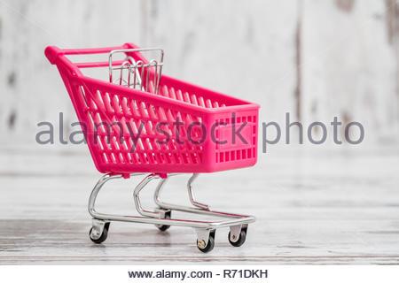 Miniatur Rosa Spielzeug Warenkorb auf weißem Hintergrund - Stockfoto