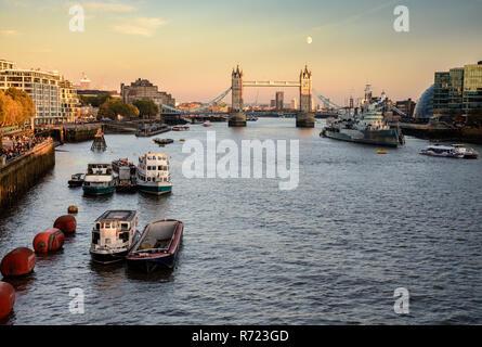 London, England, UK - Oktober 20, 2018: Der Mond erhebt sich über Londons ikonischen Tower Bridge vor dem Hintergrund der Luftverschmutzung. - Stockfoto
