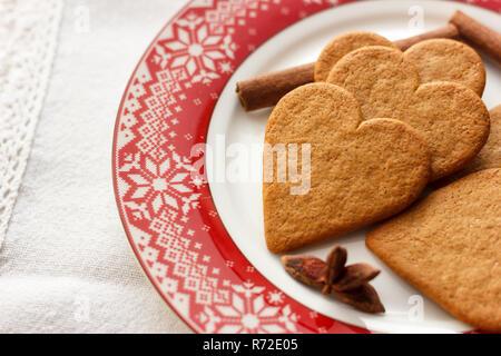 Lebkuchen heart-shaped Cookies mit Zimtstangen und Anis Sterne auf rote Platte - Stockfoto