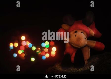 Weihnachten Rentier toy Bär sitzend auf Moss, vor der Weihnachtsbeleuchtung. - Stockfoto