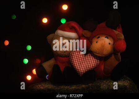 Weihnachten Teddybären und Rentier, sitzend auf Moss und halten ein Herz, vor der Weihnachtsbeleuchtung. - Stockfoto