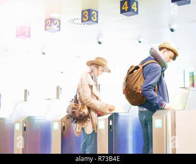 Junges Paar am Flughafen, Rucksäcke tragen, zu Fuß durch Drehkreuze - Stockfoto