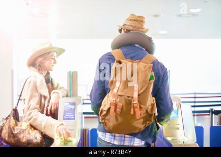 Junges Paar am Flughafen, Rucksäcke tragen, zu Fuß durch Drehkreuz - Stockfoto