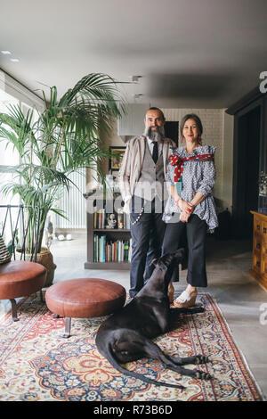 Paar mit ihrem Hund im Wohnzimmer zu Hause - Stockfoto