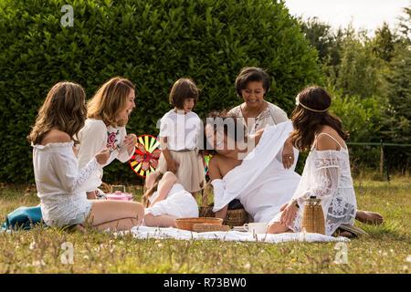 Weibliche Freunde und Familie mit Picknick im Garten - Stockfoto