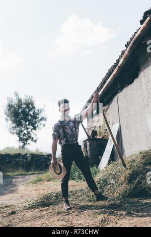 Junge männliche landwirtschaftliche Arbeiter mit Heugabel, in voller Länge Porträt - Stockfoto