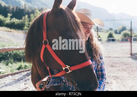 Junge cowgirl führenden Pferd in ländlichen Pferdesport Arena - Stockfoto