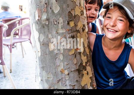 Jungen spielen durch Baum - Stockfoto