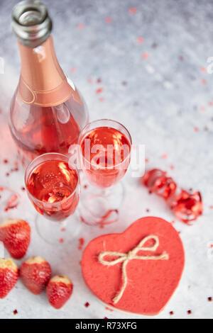 Flasche rose Champagner, Gläser mit frischen Erdbeeren und herzförmige Geschenk - Stockfoto