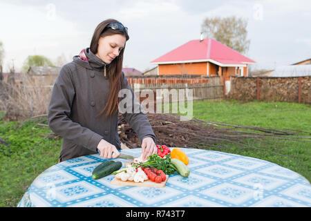 Glückliche junge Frau schneiden frisches Gemüse auf einen Tisch draußen im Garten - Stockfoto