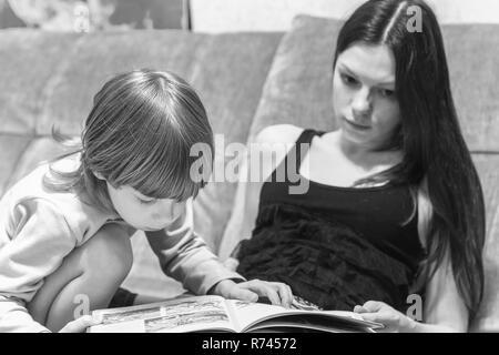 Die junge Mutter und ihr Sohn auf der Couch liegen und Geschichten aus dem Buch lesen. - Stockfoto