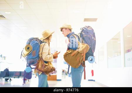 Junges Paar am Flughafen, Rucksäcke tragen, stehen von Angesicht zu Angesicht sprechen - Stockfoto