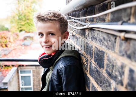 Junge lehnte sich gegen Brickwall - Stockfoto