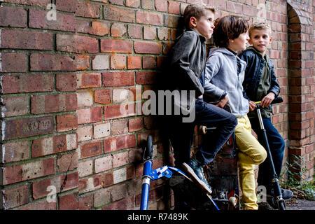 Jungen lehnte sich gegen Brickwall - Stockfoto