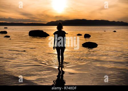 Junge Frau bei Sonnenuntergang, silhouetted Rückansicht, Quadra Island, Campbell River, Kanada - Stockfoto