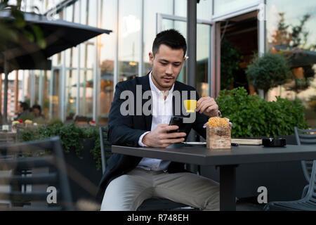 Junge Unternehmer im Straßencafé am Smartphone, Mailand, Italien suchen - Stockfoto