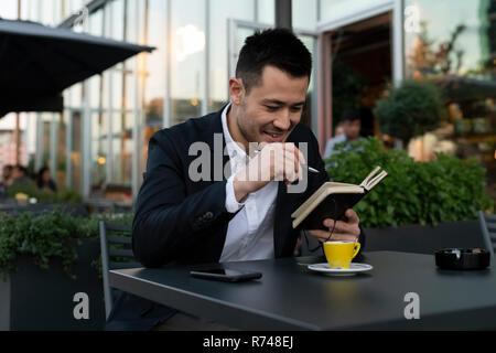 Junge Unternehmer im Straßencafé auf Notebook, Mailand, Italien - Stockfoto