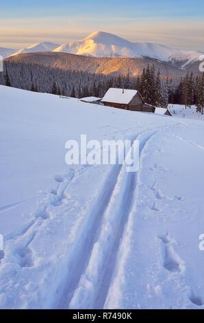 Winterlandschaft mit Ski auf dem Schnee. Sonnenaufgang in den Bergen. Holz- Dorf der Hirten. Karpaten, Ukraine, Europa - Stockfoto