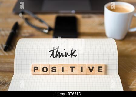 Nahaufnahme auf das Notebook um Holz Tisch Hintergrund, Ausrichtung auf die Holzblöcke mit Buchstaben, Positiv Denken text - Stockfoto