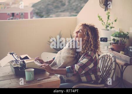Schöne kaukasische Frau mittleren Alters mit einem alten Vintage Schreibmaschine wie ein modernes Blogger auf Papier während ihrer reizenden bester Freund mops Hund ihr Witz küssen - Stockfoto