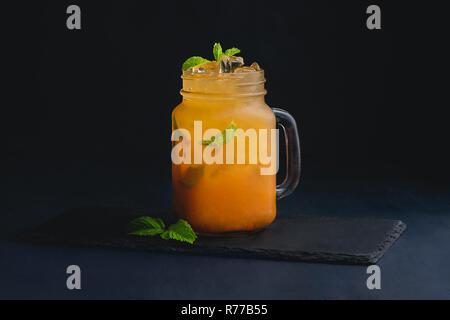 Ice Cold citrus Cocktail in einer vintage Glas Marmeladenglas. Der dunkle Hintergrund mit Kopie Raum für ein Menü. Stockfoto