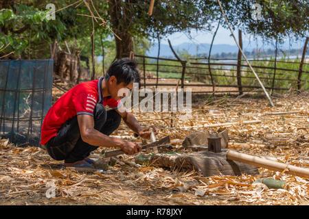 Don Daeng, Laos - 27. April 2018: Lokaler Mann Schneiden von Holz in einem abgelegenen wilde Gegend der ländlichen Laos - Stockfoto