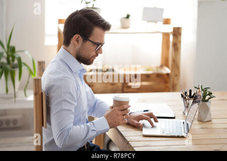 Fokussierte männliche Mitarbeiter am Laptop Kaffee trinken arbeiten - Stockfoto