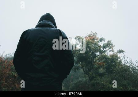 Suchen von hinten an eine geheimnisvolle vermummte Abbildung nass vom Regen auf ein Land weg. - Stockfoto