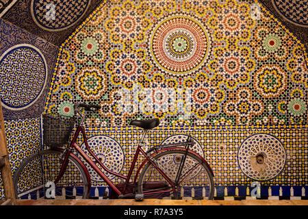 Marokko, Fes, Fes el Bali, Medina, Fahrrad in Seqqaya öffentlichen Trinkbrunnen mit traditionellen zellij Fliesen- Dekoration - Stockfoto