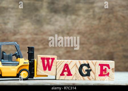Gelb Spielzeug Gabelstapler Buchstaben gedrückt. block w Wort Lohn auf Holz Hintergrund abzuschließen - Stockfoto