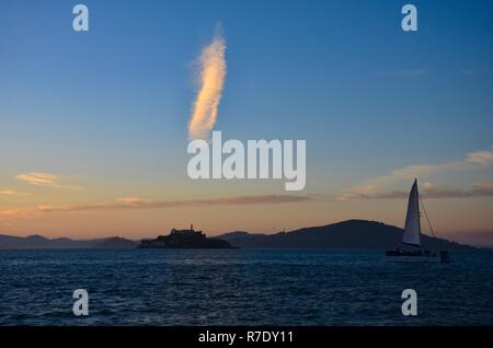 Blick vom Pier 39 in Richtung Insel Alcatraz auf Sonnenuntergang, Touristen genießen Sie ein Segelboot Fahrt - Stockfoto