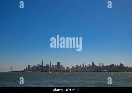 Blick von Alcatraz Island auf die Skyline von San Francisco, Oakland Bay Bridge auf der linken Seite, bucht, blauer Himmel, sonnig, Segelboote - Stockfoto