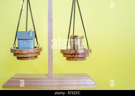 Waagen mit Imitation des Hauses in Form einer Metall Schlüsselanhänger und Münzen auf gelbem Hintergrund. Das Konzept der spart Geld für ein Haus zu kaufen. Kopieren - Stockfoto