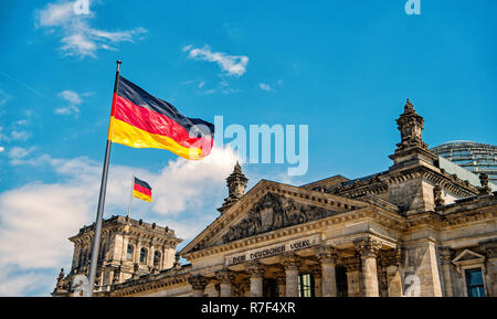 Deutsche Fahnen im Wind am berühmten Reichstag, Sitz des deutschen Parlaments Deutscher Bundestag, an einem sonnigen Tag mit blauen Himmel und Wolken, zentrale Berlin Mitte, Deutschland - Stockfoto