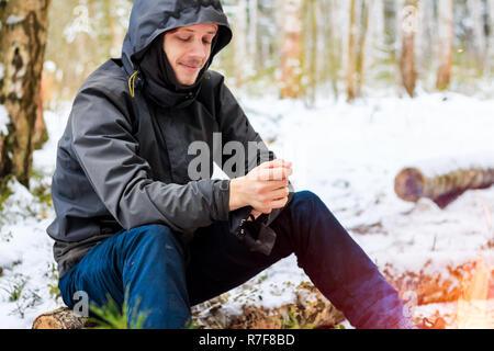 Junger Mann sitzt auf einem Baumstamm im Winter - Stockfoto