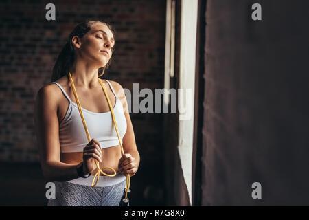 Sportlerin mit springseile um ihren Hals steht die Turnhalle Fenster. Fitness Frau, die nach dem Training im Fitnessraum. - Stockfoto