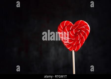 Rote Lutscher in Form von Herzen auf dunklem Hintergrund mit kopieren. Liebe und romantische Hintergrund - Stockfoto