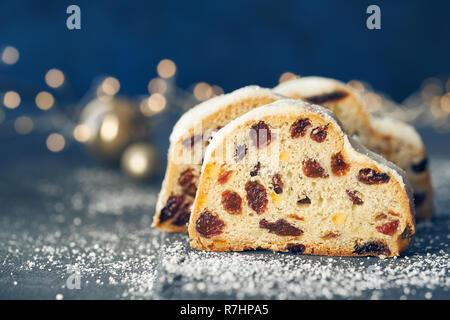 Christstollen auf dunkelblauem Hintergrund mit festlichen Weihnachtsbeleuchtung. Traditionelle deutsche Dessert für Weihnachten feiern.