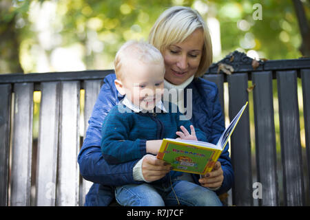 Mutter und Sohn sind ein Buch auf einer Parkbank - Stockfoto