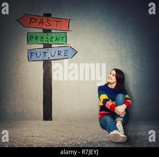 Junge Frau auf dem Boden sitzend auf einem Wegweiser mit Pfeilen, die Vergangenheit, die Gegenwart und die Zukunft zeigt. Verloren in der Zeit bunte Schild, Schicksal evolu - Stockfoto