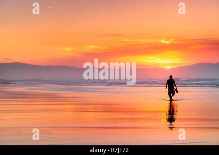 Einsame Person zu Fuß am Strand an der schönen roten Sonnenuntergang - Stockfoto