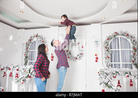Junge gerne Vater wirft kleine Sohn mit Mutter in Weihnachten Dekoration - Stockfoto