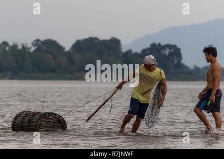 Don Daeng, Laos - 27. April 2018: Zwei Männer in der Dämmerung Fische fangen in einer abgelegenen Insel des Mekong in Laos. - Stockfoto