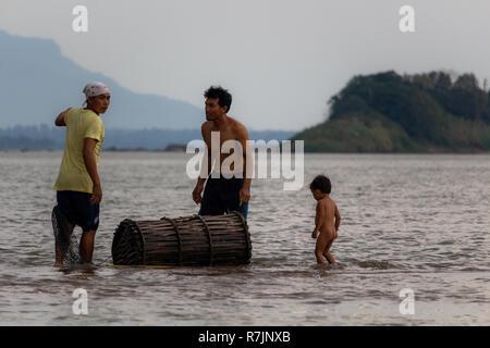 Don Daeng, Laos - 27. April 2018: Zwei Männer und ein Kind in der Dämmerung Fische fangen in einer abgelegenen Insel des Mekong in Laos. - Stockfoto