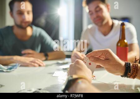 Nahaufnahme der männlichen Händen hält zwei Trümpfe beim Spielen in Karten mit seinen Freunden am Tisch - Stockfoto