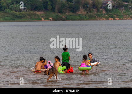 Don Daeng, Laos - 27. April 2018: Die Einheimischen schwimmen im Fluss Mekong bei Sonnenuntergang - Stockfoto