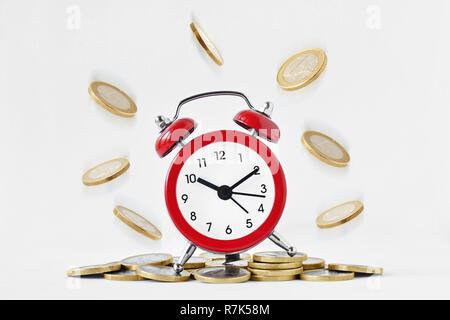 Wecker mit herabfallenden Münzen auf weißem Hintergrund - Zeit ist Geld Konzept