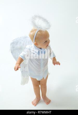 Eine Urlaubsatmosphäre. Baby Engel. Adorable kleine Engel Junge. Kleiner Junge mit Engel Flügel und Heiligenschein. Cute valentines Cupid oder cherub Baby. Weihnachten Engel. Christmas Party Feier - Stockfoto