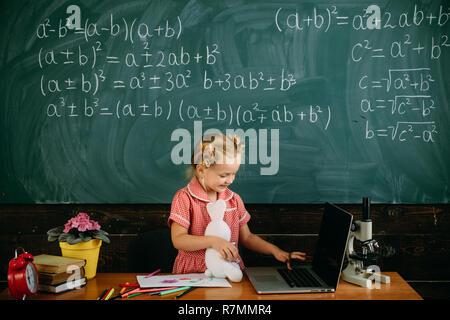 Mädchen mit Laptop an der Lektion. Kleines Kind Tastatur des Laptops in der Schule. Ihr persönlicher Assistent - Stockfoto