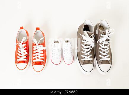 Konzeptionelle Bild von Gumshoes sneakers von Vater, Mutter und Sohn Tochter auf weißem Hintergrund Kopie Raum in verschiedenen Größen in Zweisamkeit isoliert Fam - Stockfoto